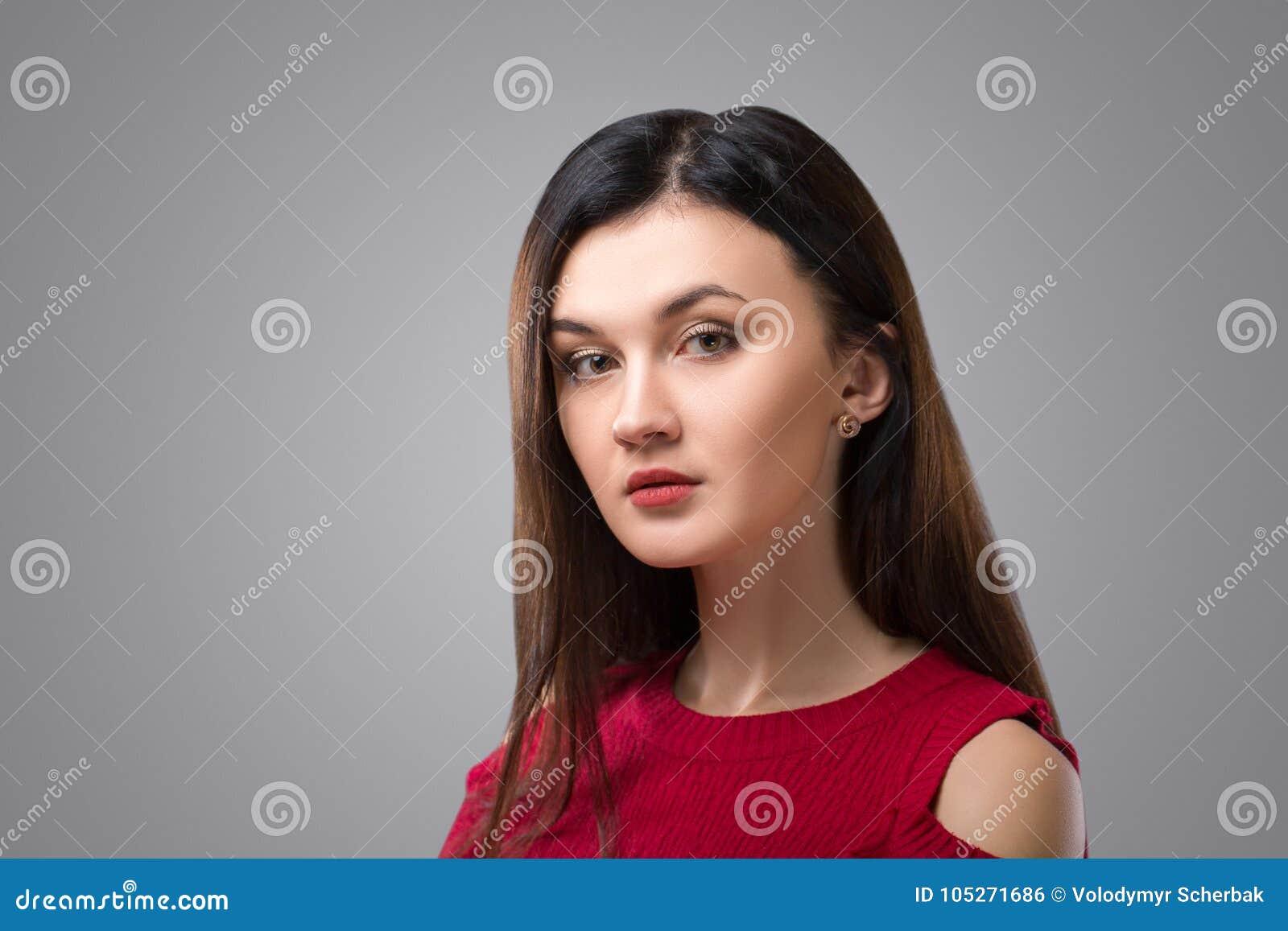 Όμορφη γυναίκα brunette στο κόκκινο φόρεμα στο γκρίζο υπόβαθρο