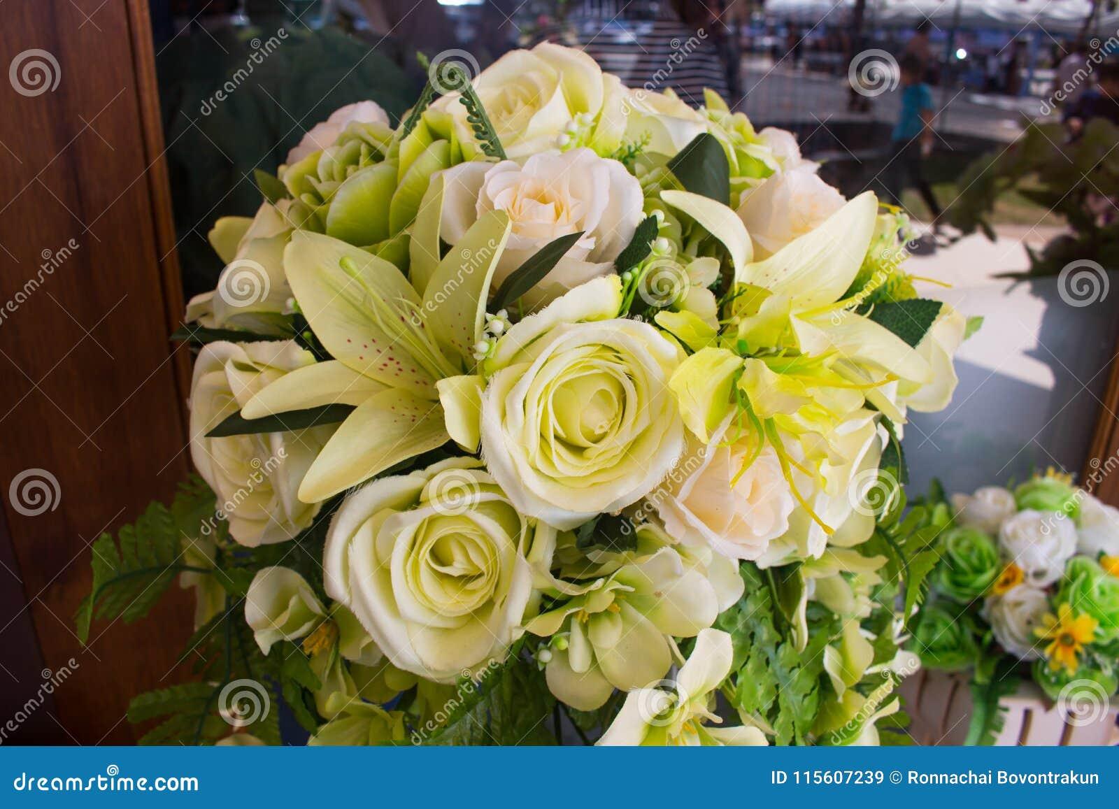 Όμορφη διακόσμηση στο γαμήλιο πίνακα με τα τριαντάφυλλα στην ανθοδέσμη