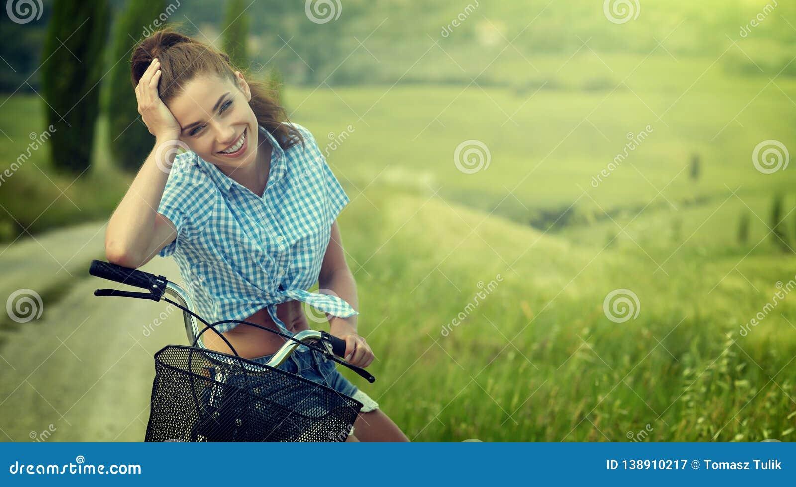 Όμορφη εκλεκτής ποιότητας συνεδρίαση κοριτσιών δίπλα στο ποδήλατο, θερινός χρόνος