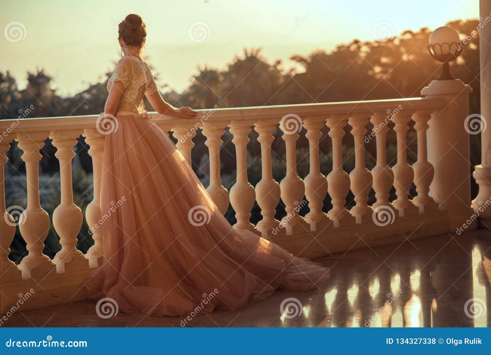 Όμορφη κυρία στο πολυτελές φόρεμα αιθουσών χορού με τη φούστα του Tulle και τη δαντελλωτός κορυφή που στέκονται στο μεγάλο μπαλκό