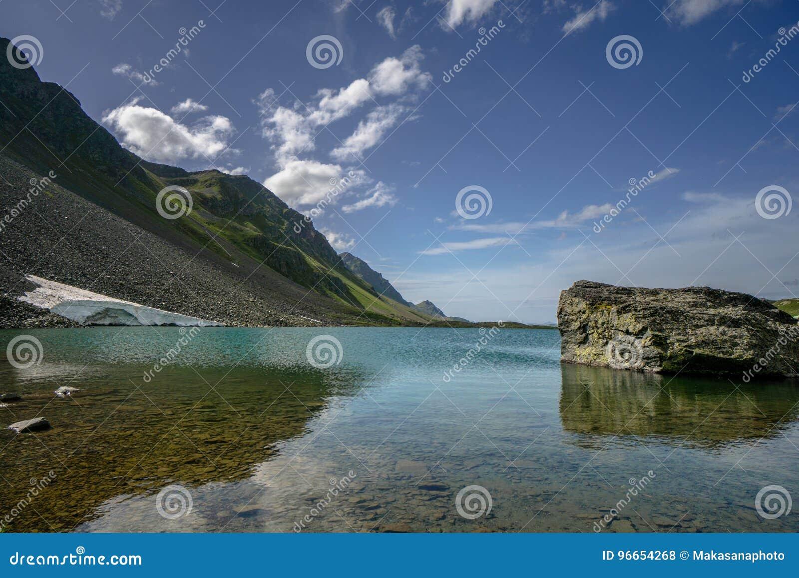 Όμορφη λίμνη βουνών κοντά σε Davos με έναν μεγάλο λίθο στο πρώτο πλάνο