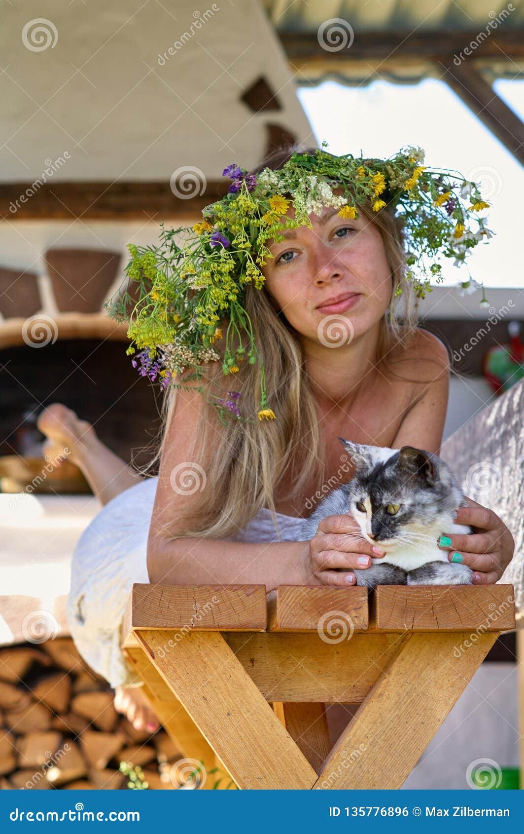 Όμορφη μακρύς-άσπρη γυναίκα τρίχας στο άσπρο στεφάνι φορεμάτων και λουλουδιών που βρίσκεται σε έναν ξύλινο πάγκο με τη χαριτωμένη