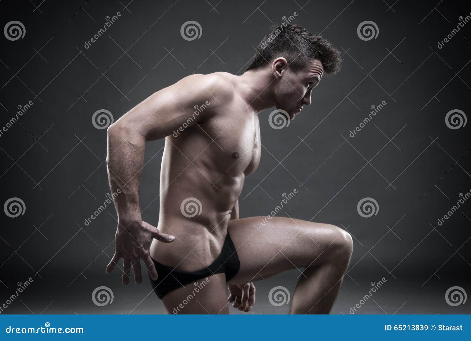Όμορφη μυϊκή τοποθέτηση bodybuilder στο γκρίζο υπόβαθρο Συγκρατημένος πυροβολισμός στούντιο