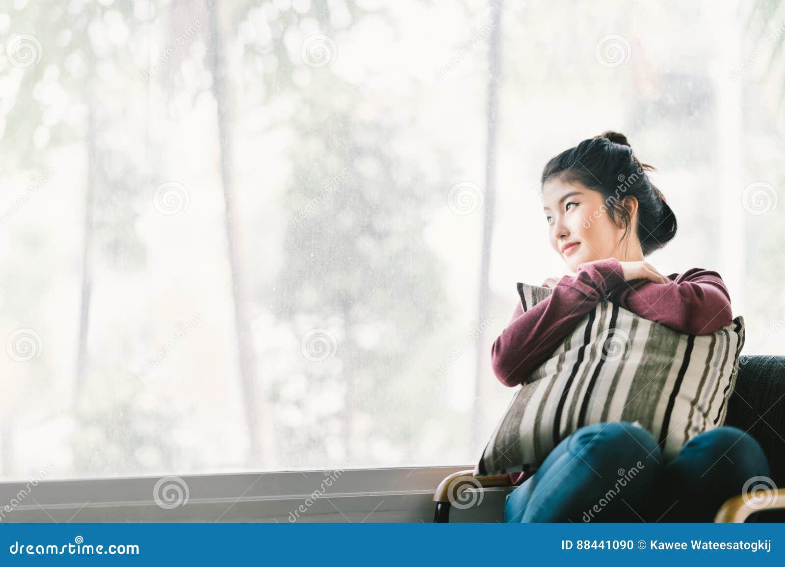 Όμορφη νέα ασιατική χαλάρωση κοριτσιών στο σπίτι, καθμένος μόνο από το παράθυρο, που εξετάζει το διάστημα αντιγράφων