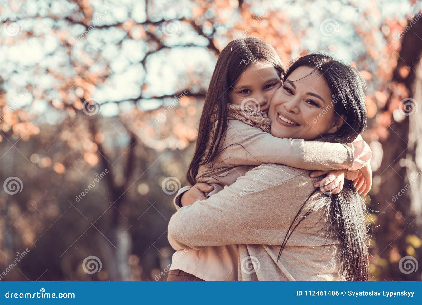 Όμορφη νέα γυναίκα και το παιδί της στον κήπο φθινοπώρου