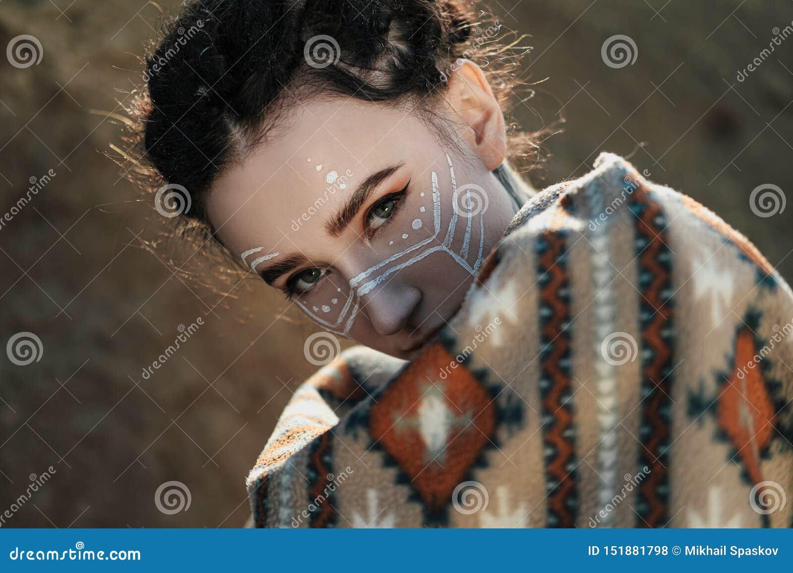 Όμορφη νέα γυναίκα με τα αυτιά νεραιδών, dreadlocks και εθνικό poncho, με το χρωματισμένο πρόσωπο Τοποθέτηση ενάντια σε μια αμμώδ