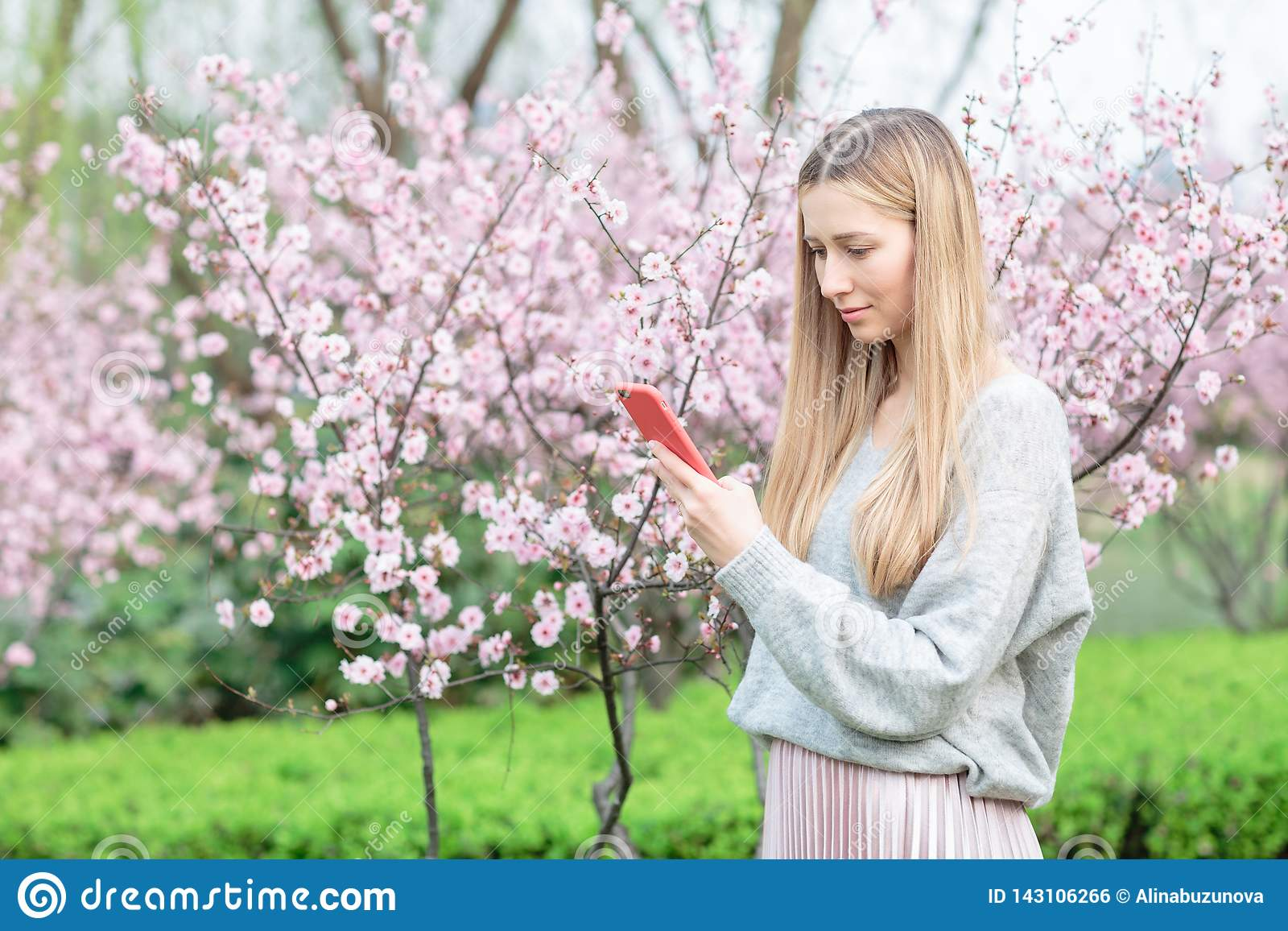 Όμορφη νέα γυναίκα με τη μακριά ξανθή τρίχα που χρησιμοποιεί το κινητό τηλέφωνο στο πάρκο με το ανθίζοντας δέντρο