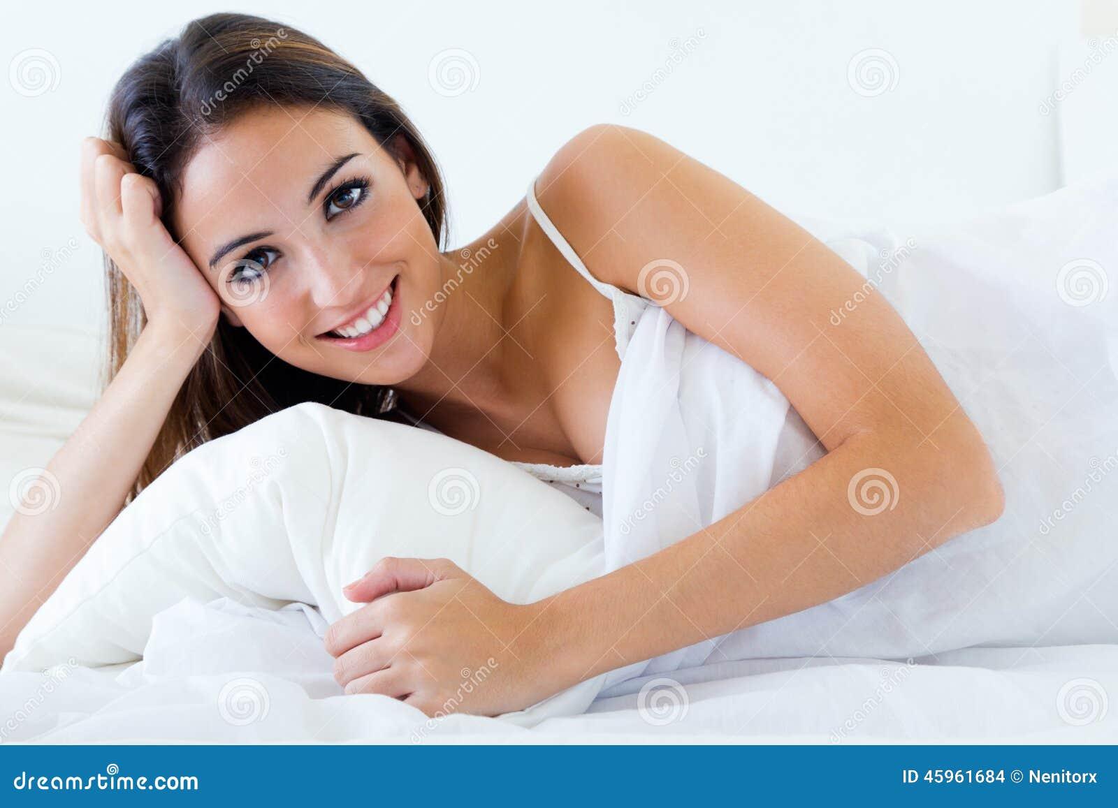 Όμορφη νέα γυναίκα που βρίσκεται στο κρεβάτι Απομονωμένος στο λευκό