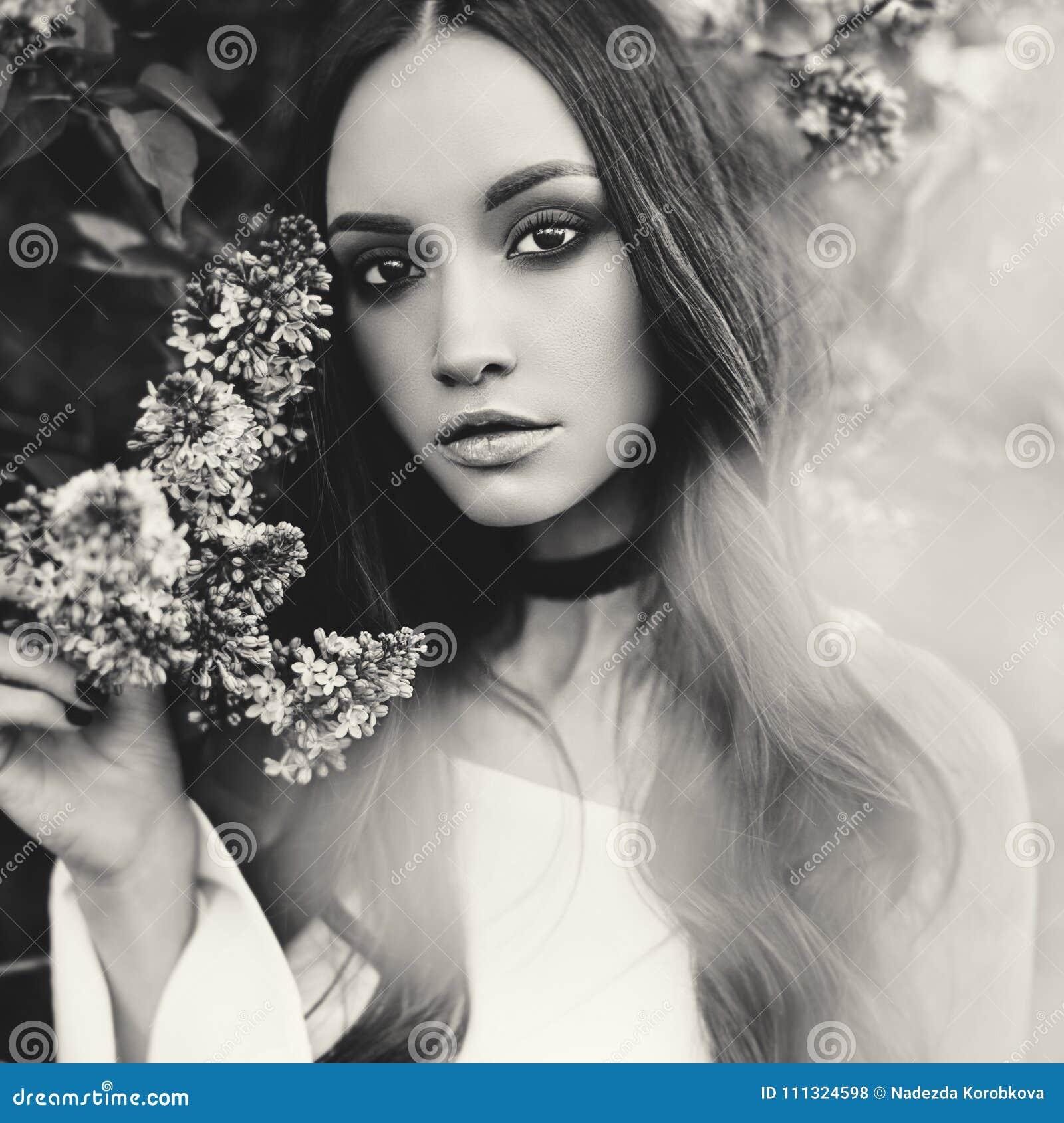 b2a998e8263 Όμορφη νέα γυναίκα που περιβάλλεται από τα λουλούδια της πασχαλιάς ...