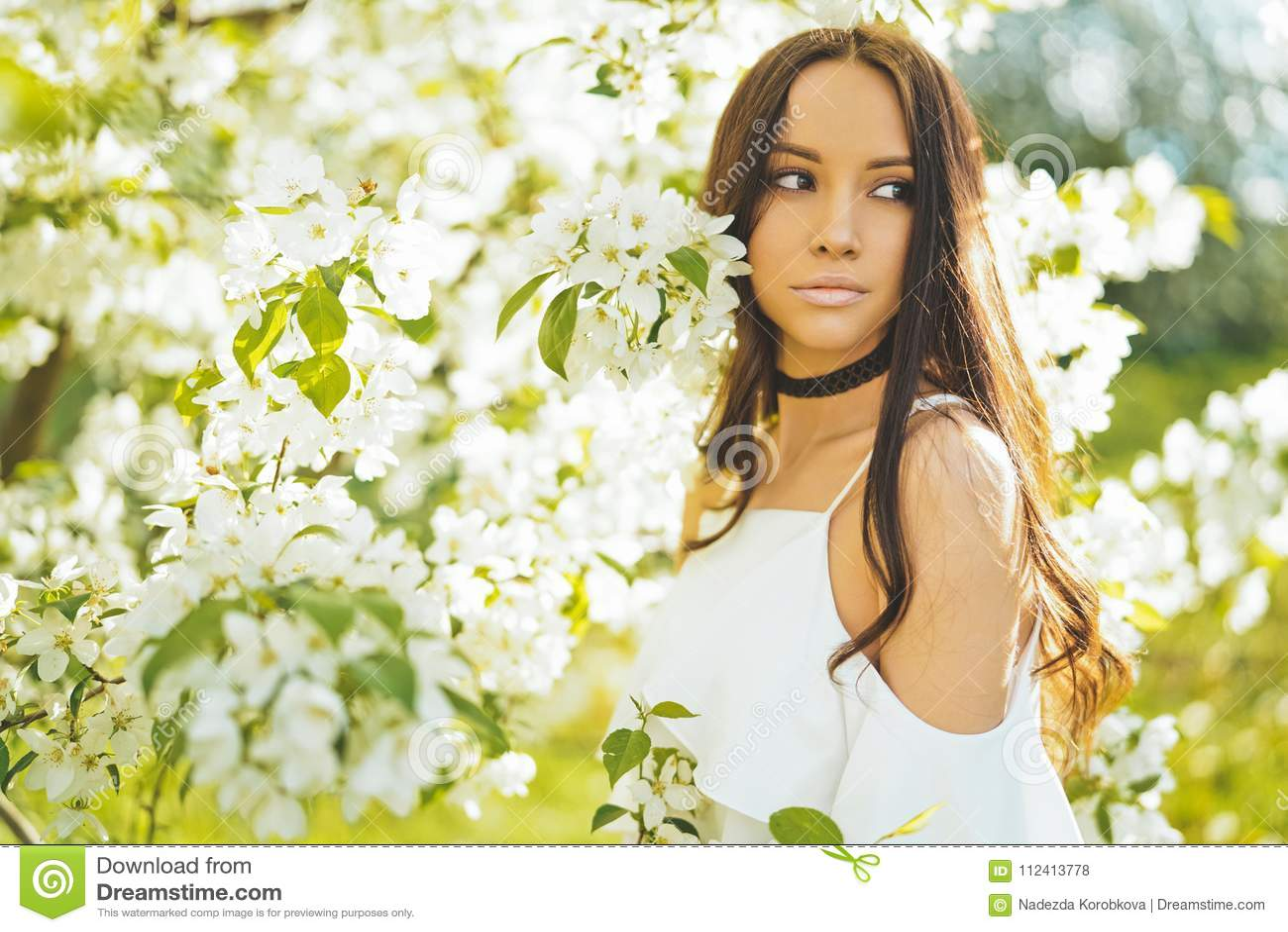 0babbaf5a20 Όμορφη νέα γυναίκα που περιβάλλεται από τα λουλούδια του Apple ...