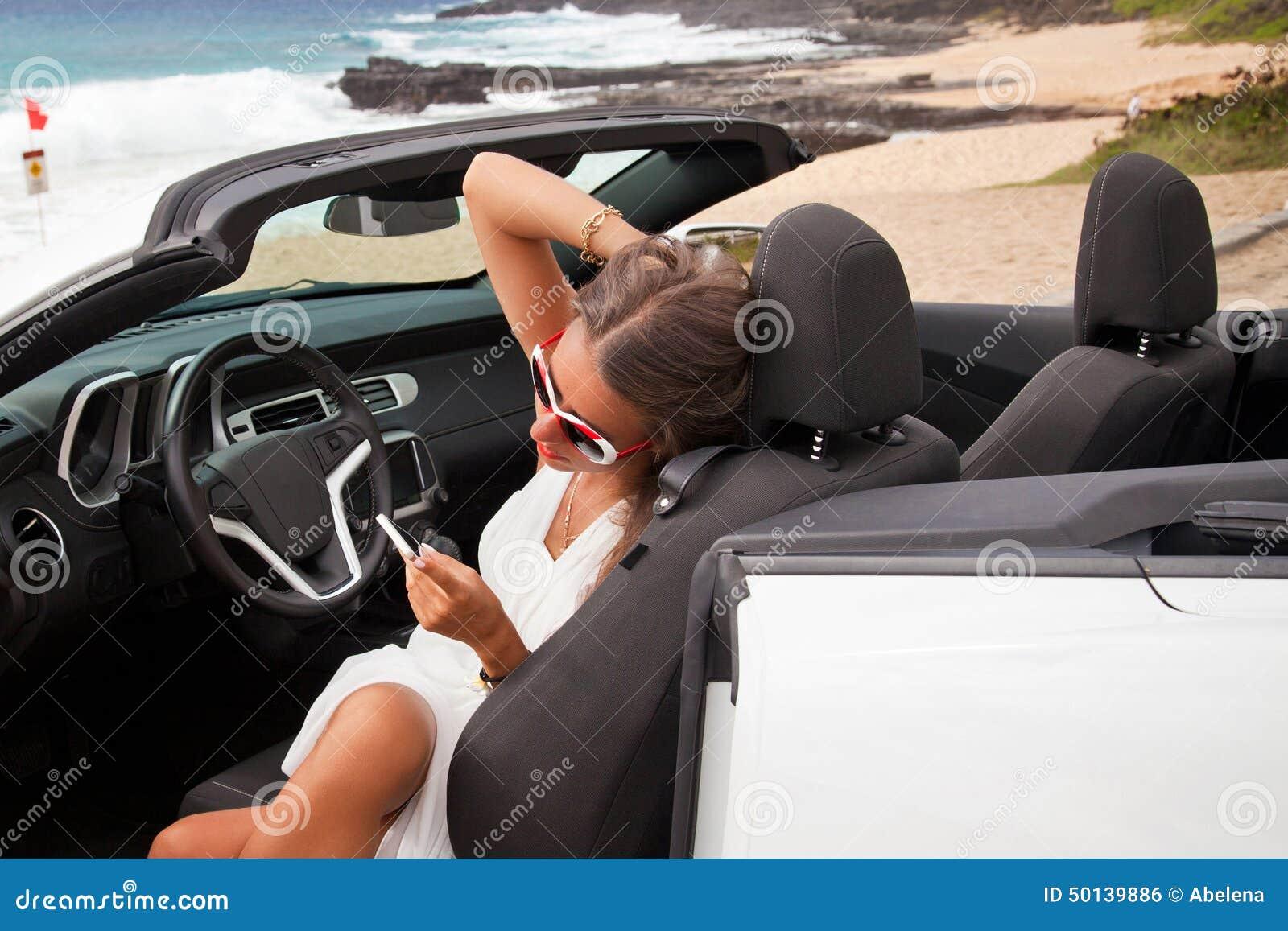 Όμορφη νέα γυναίκα που στηρίζεται στο αυτοκίνητό της