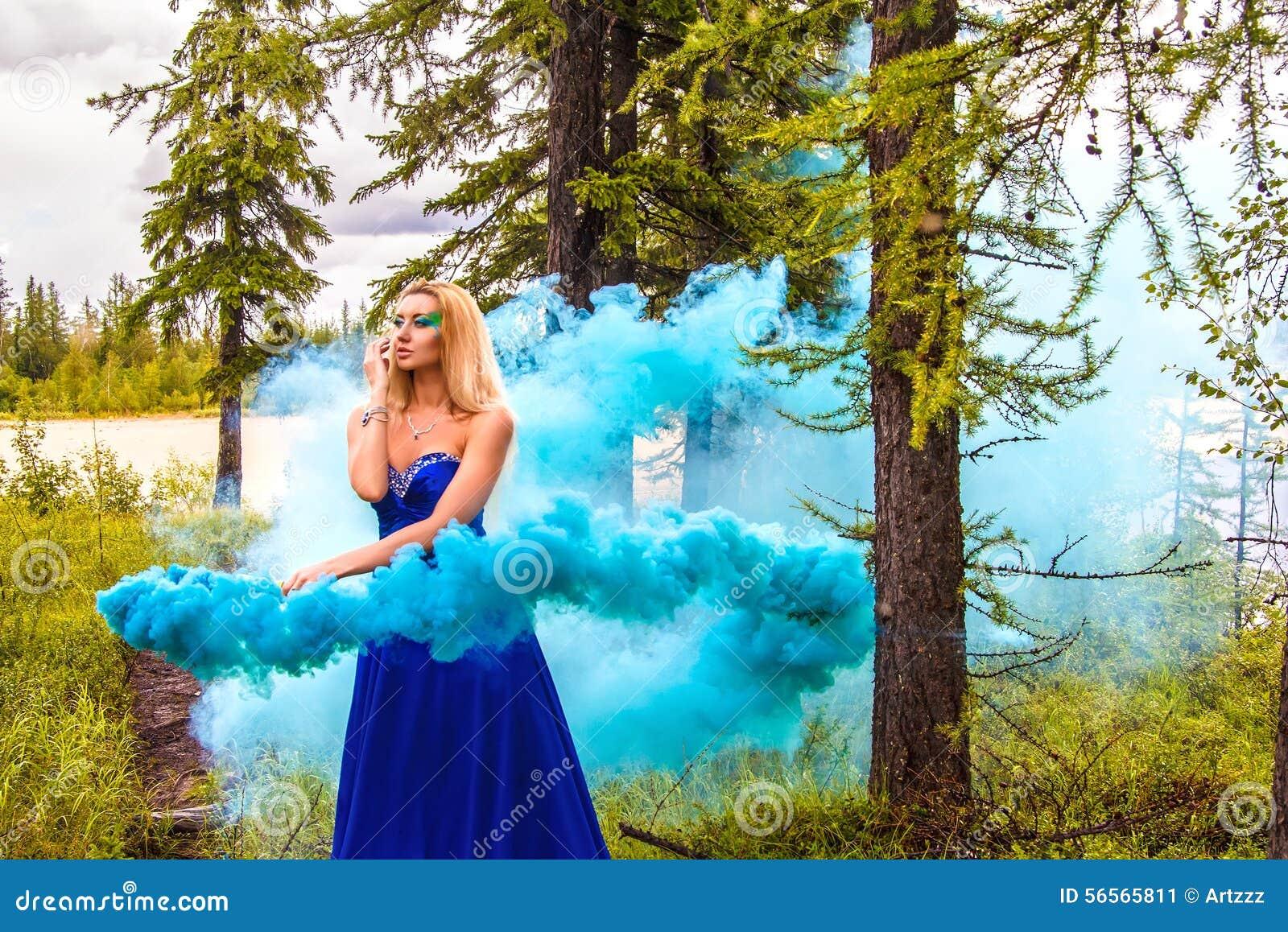 Όμορφη νέα γυναίκα σε ένα σύννεφο ενός φωτεινού μπλε καπνού