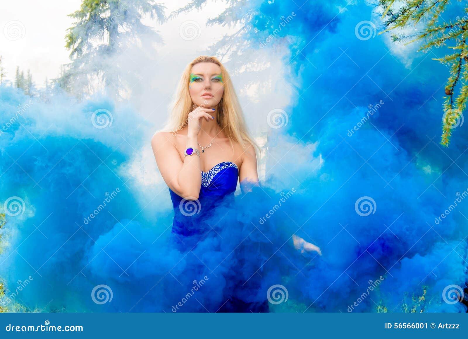 Download Όμορφη νέα γυναίκα σε ένα σύννεφο ενός φωτεινού μπλε καπνού Στοκ Εικόνα - εικόνα από καυκάσιος, φόρεμα: 56566001