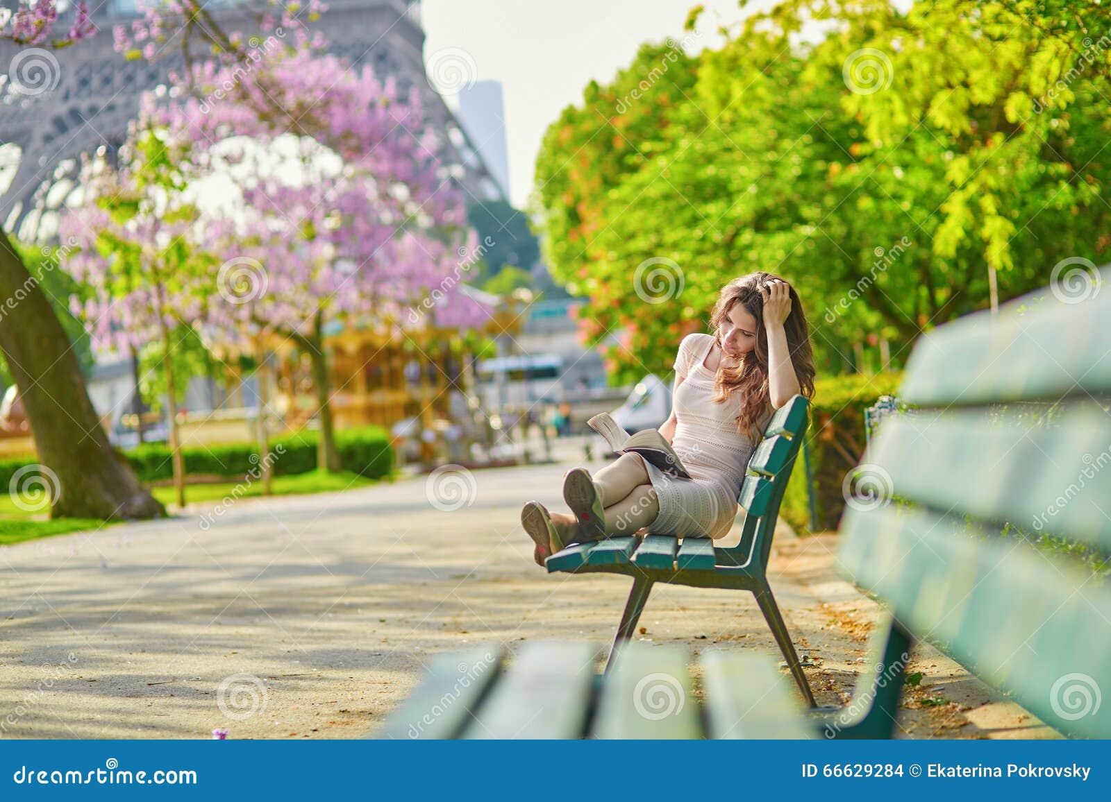 Όμορφη νέα γυναίκα στην ανάγνωση του Παρισιού στον πάγκο υπαίθρια