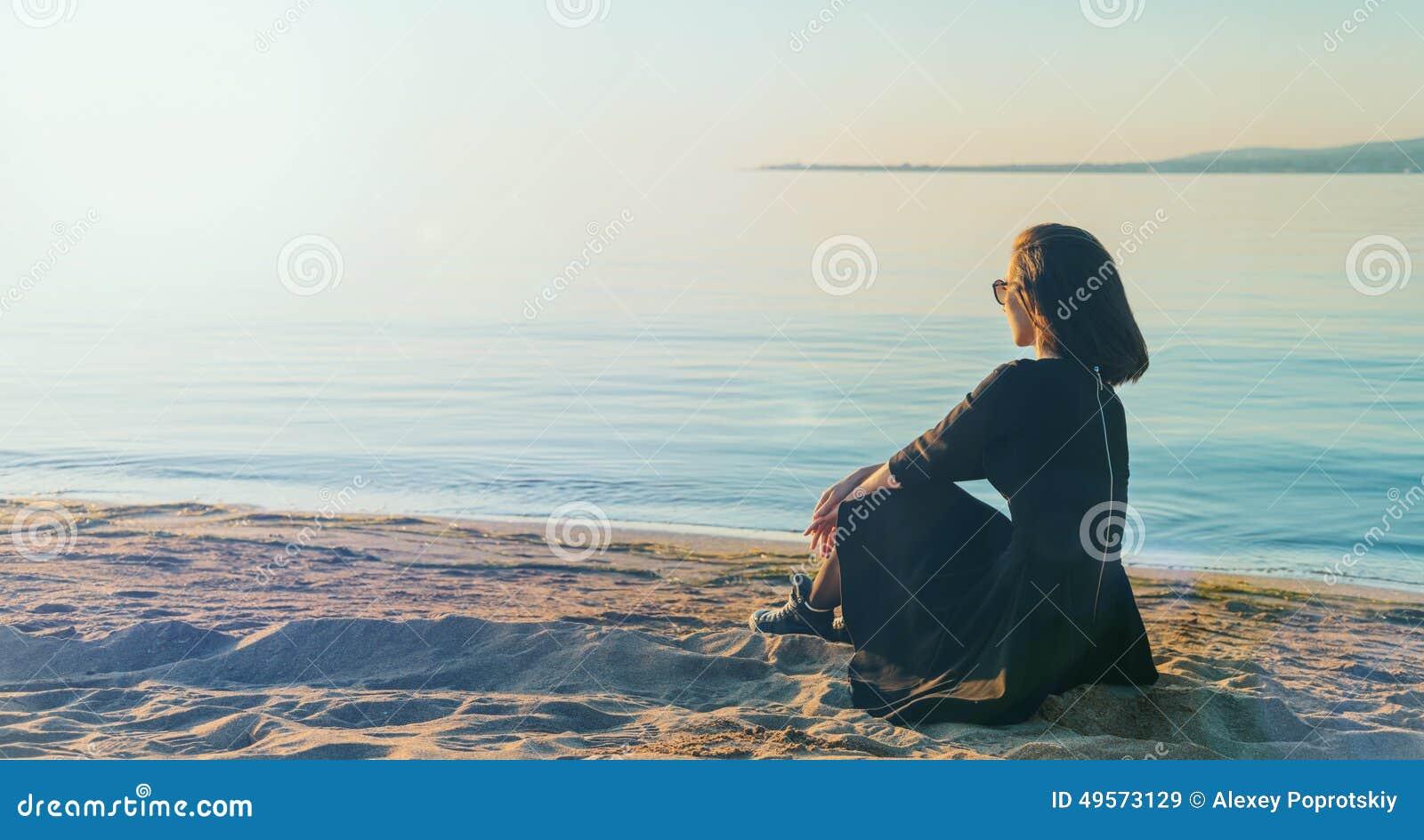 Όμορφη νέα γυναίκα στη συνεδρίαση φορεμάτων στην παραλία