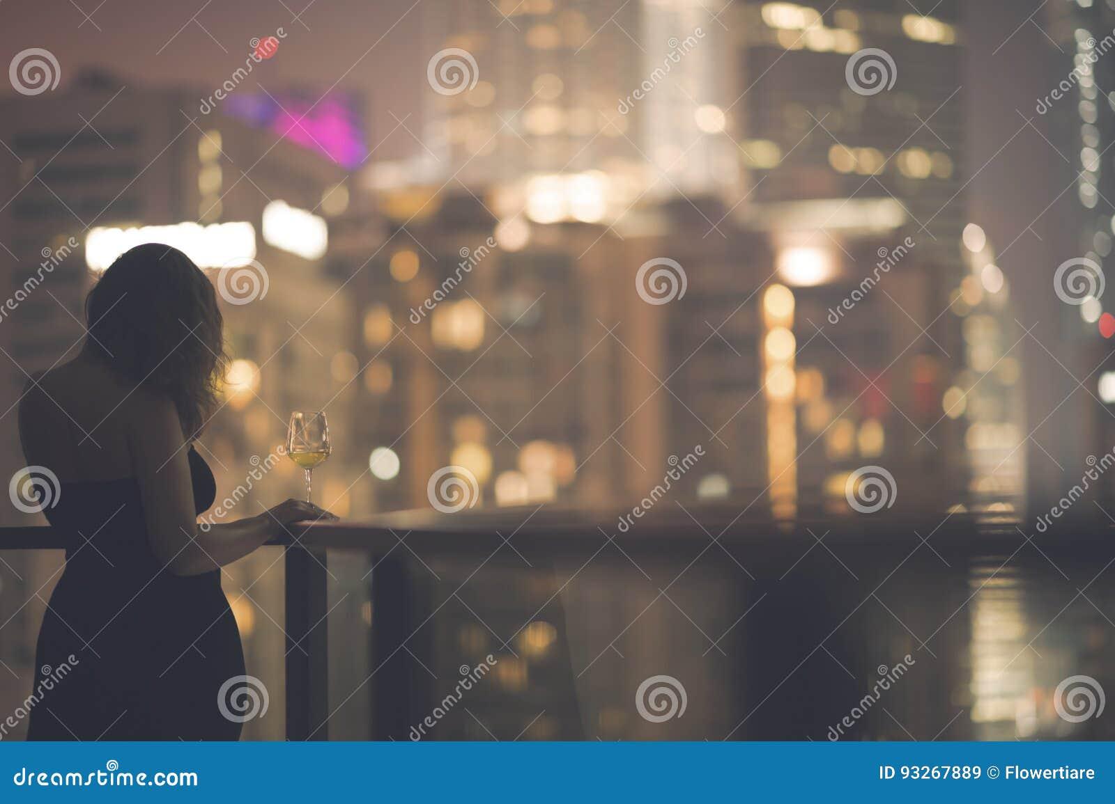cdd943b20195 Όμορφη νέα γυναίκα στο μπαλκόνι σε ένα μαύρο φόρεμα με ένα ποτήρι του  κρασιού στο υπόβαθρο