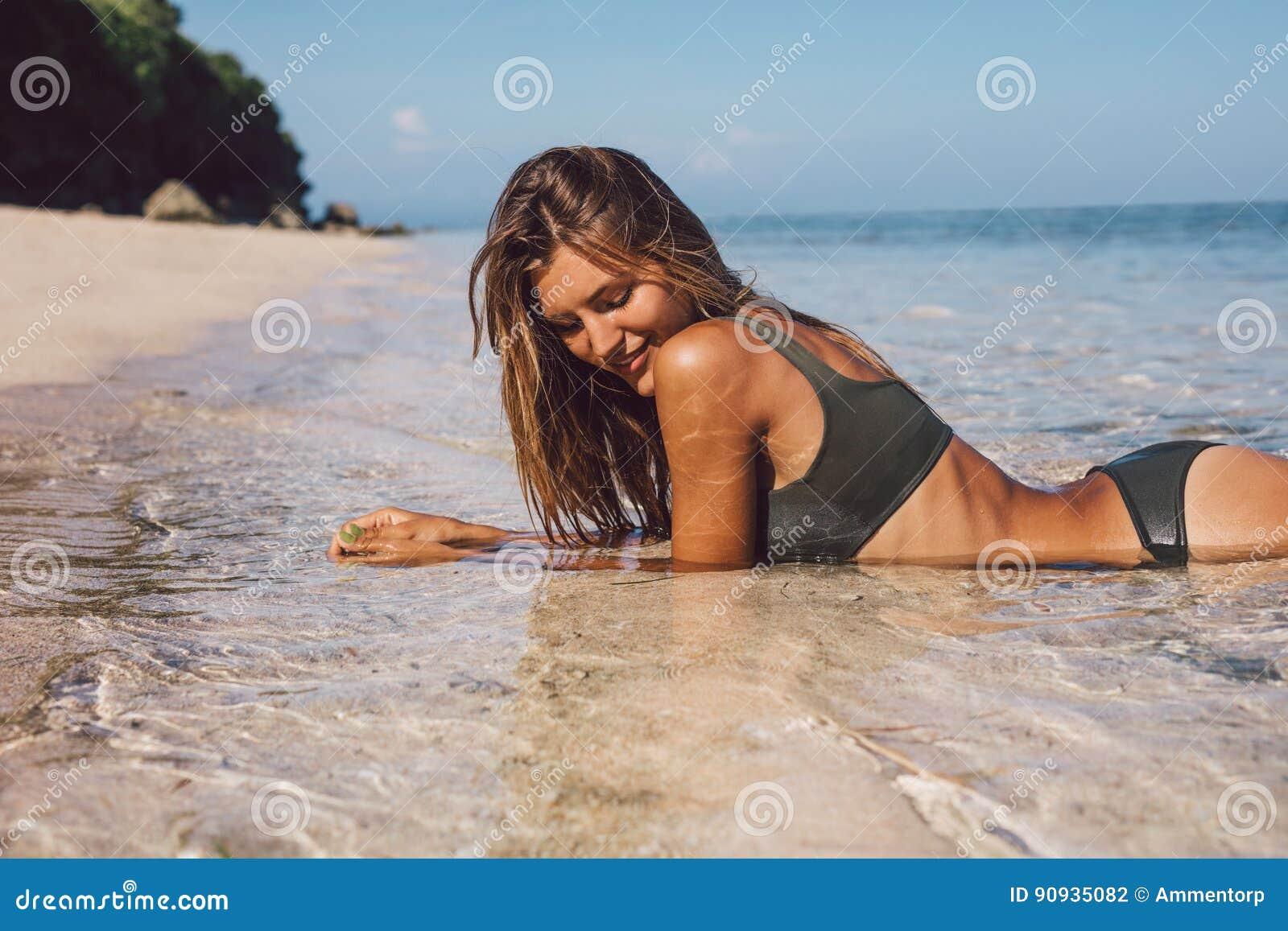 Όμορφη νέα γυναίκα στο μπικίνι που βρίσκεται στην παραλία