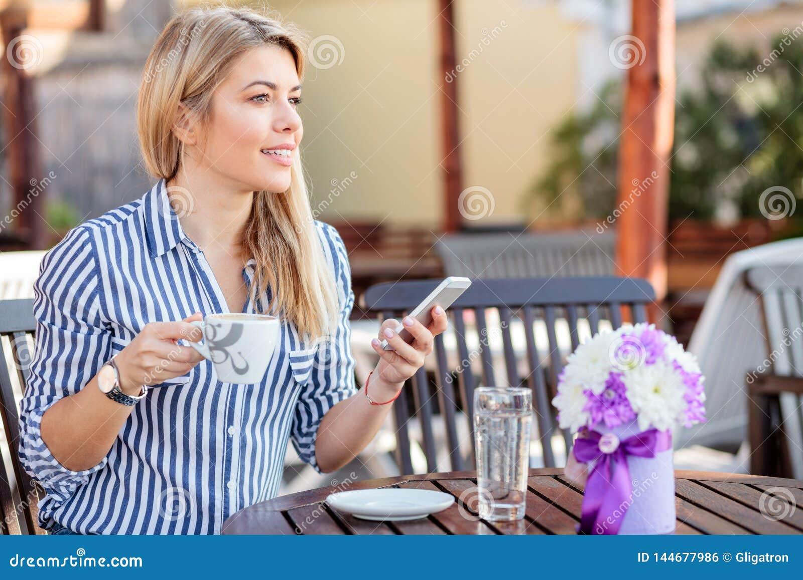 Όμορφη νέα γυναίκα χρησιμοποιώντας το έξυπνο τηλέφωνο και πίνοντας το