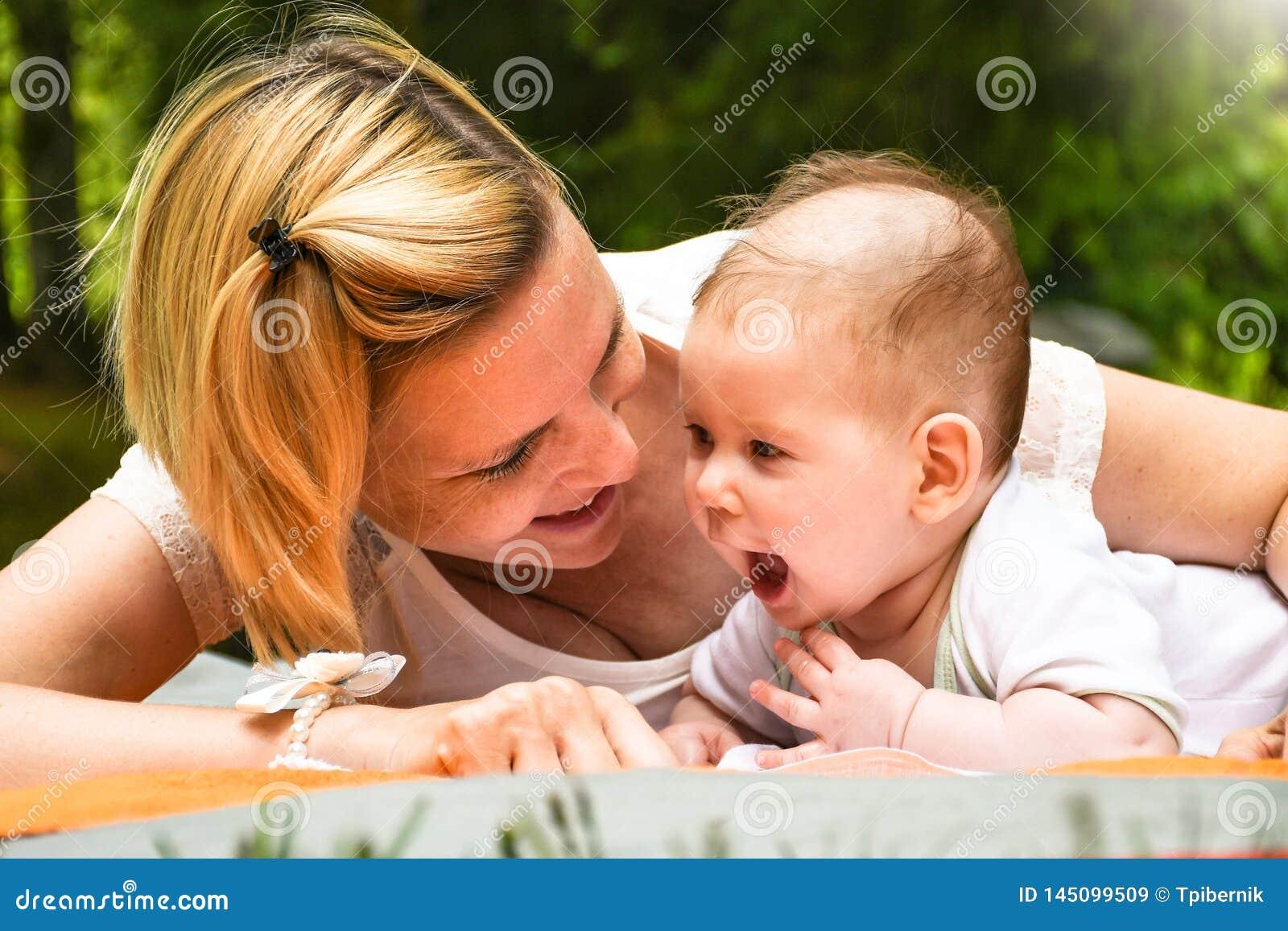 Όμορφη νέα ευτυχής μητέρα με τα ξανθά μαλλιά που βάζουν στο κάλυμμα και που παίζουν με το νεογέννητο μωρό της