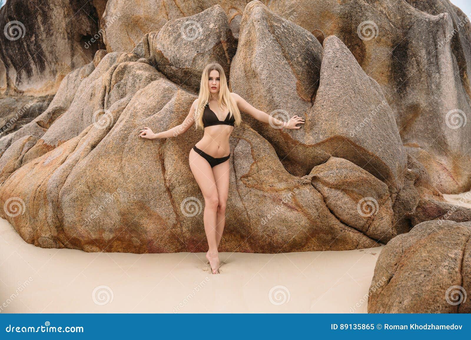 Όμορφη νέα ξανθή γυναίκα στη μαύρη τοποθέτηση μπικινιών στην παραλία Προκλητικό πρότυπο πορτρέτο με το τέλειο σώμα Έννοια