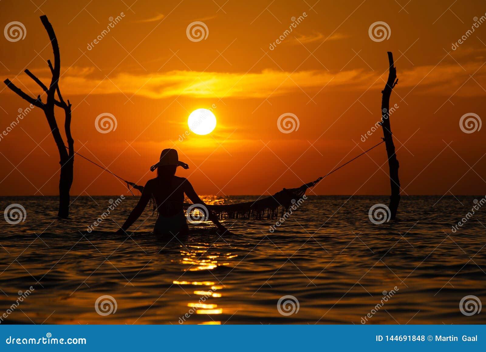 Όμορφη νέα σκιαγραφία γυναικών με την τοποθέτηση ταλάντευσης στη θάλα