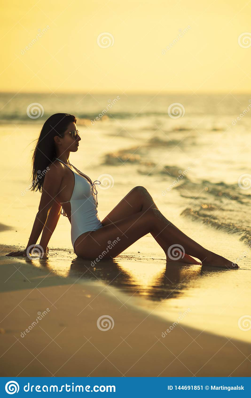 Όμορφη νέα τοποθέτηση γυναικών στην άσπρη παραλία, όμορφο τοπίο με τη