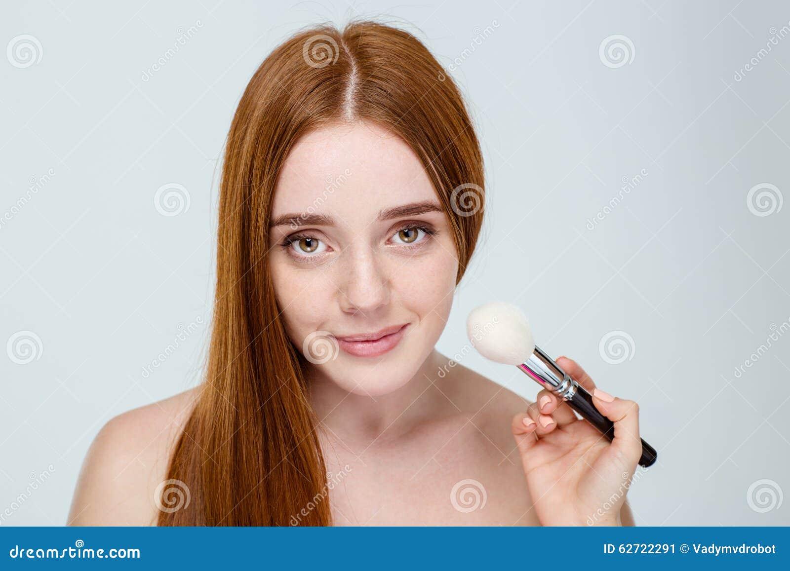 Όμορφη νέα redhead γυναίκα με το πορτρέτο φακίδων που απομονώνεται στο λευκό