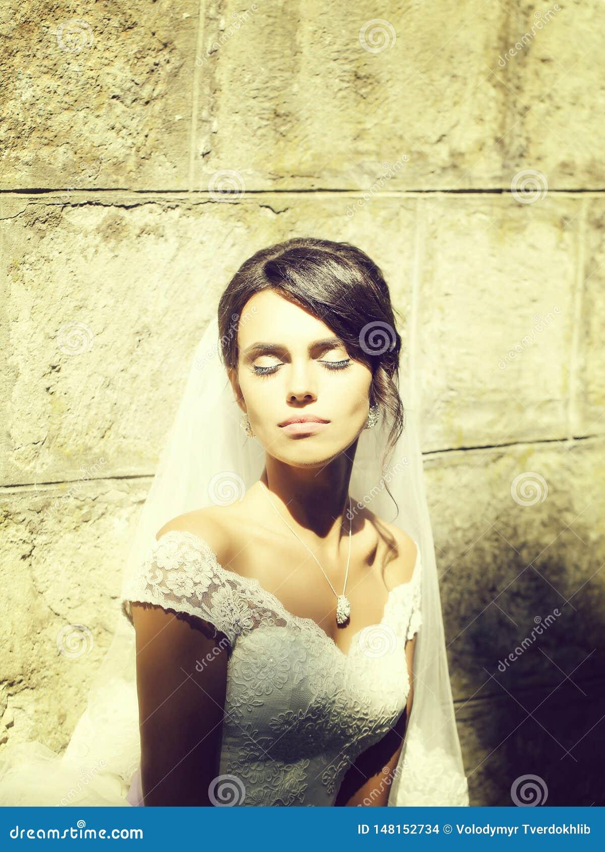Όμορφη νύφη κοντά στον πετρώδη τοίχο