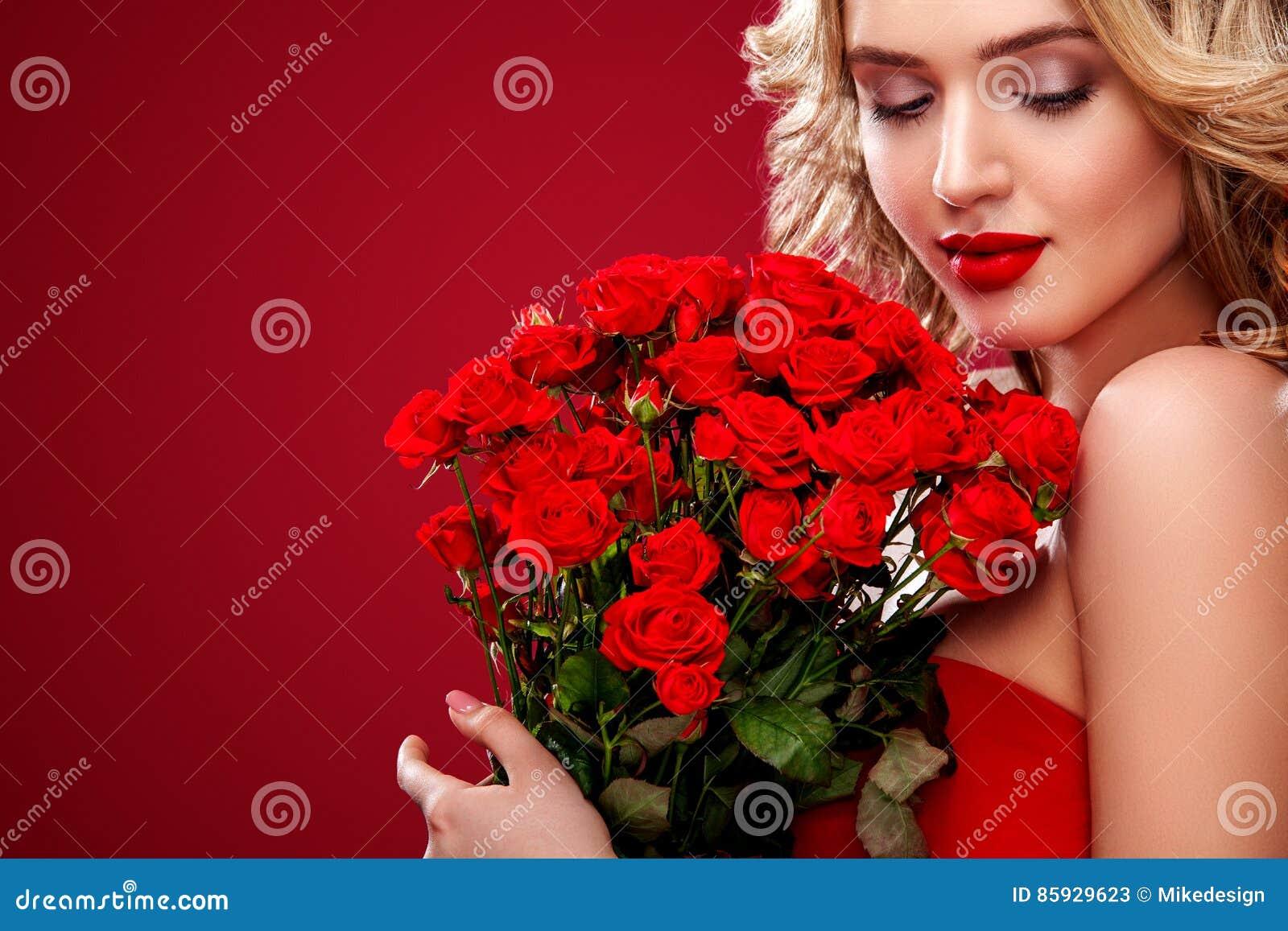 Όμορφη ξανθή ανθοδέσμη εκμετάλλευσης γυναικών των κόκκινων τριαντάφυλλων Βαλεντίνος Αγίου και διεθνής ημέρα γυναικών ` s, οκτώ Μα