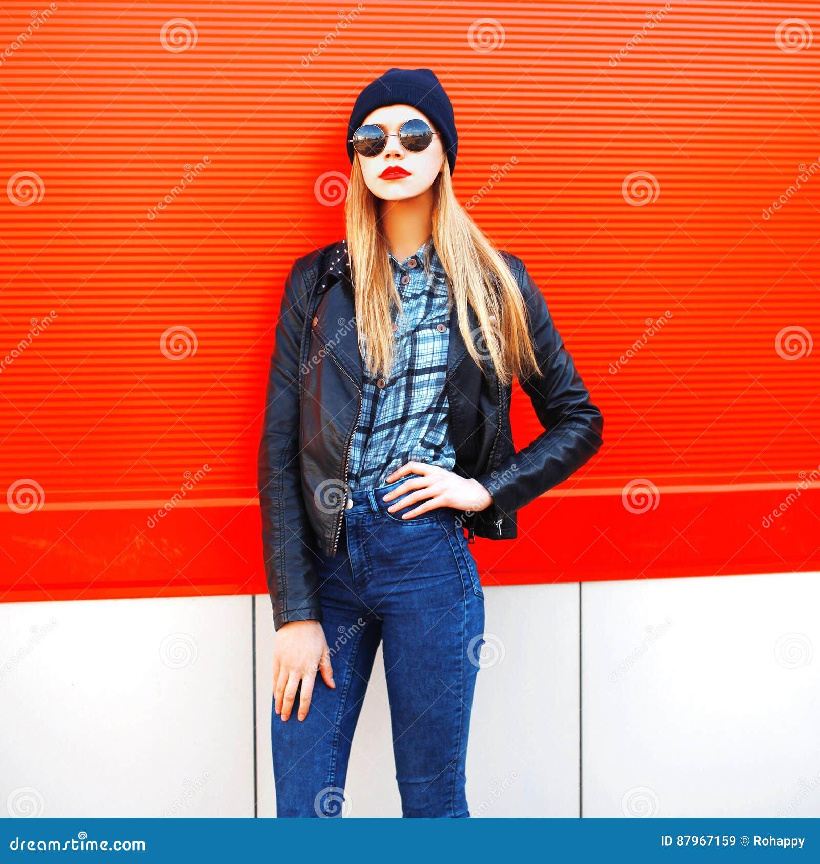 Όμορφη ξανθή γυναίκα πορτρέτου μόδας στο μαύρο ύφος βράχου σε ένα κόκκινο υπόβαθρο στην πόλη