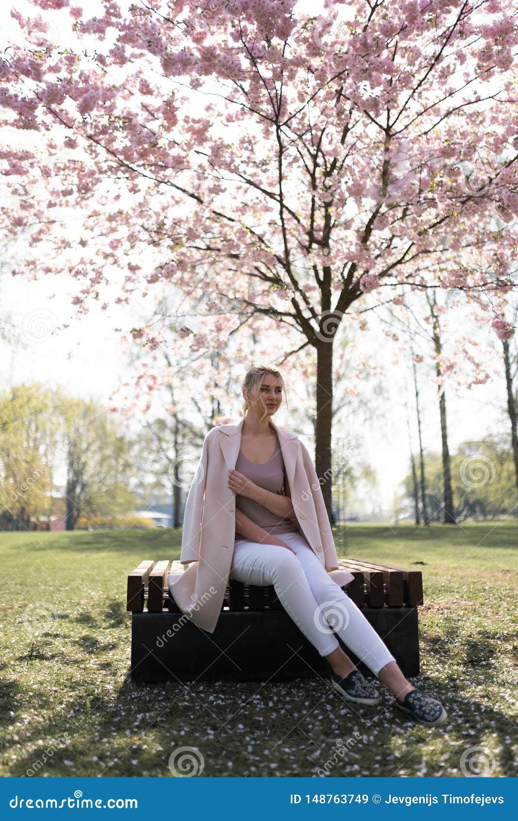 Όμορφη ξανθή νέα γυναίκα στο πάρκο ανθών κερασιών Sakura που απολαμβάνει την άνοιξη τη φύση και το ελεύθερο χρόνο κατά τη διάρκει