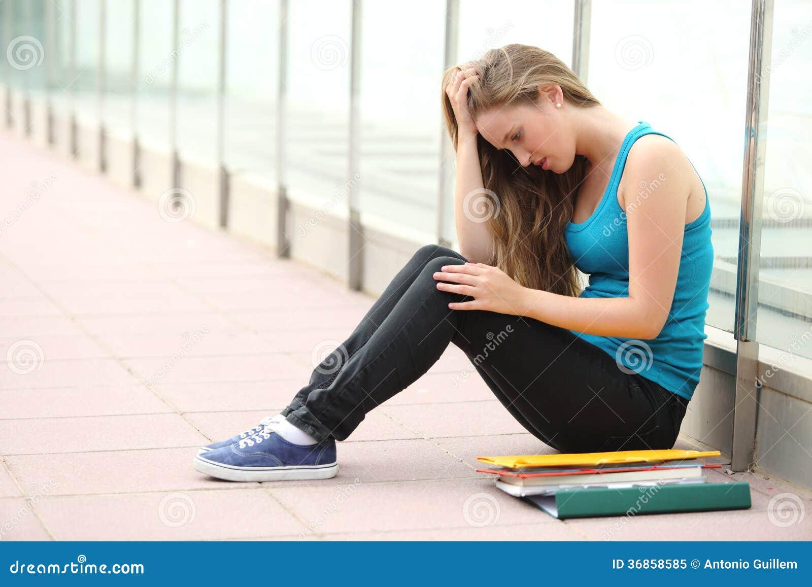 Όμορφη πιεσμένη κορίτσι συνεδρίαση εφήβων στο πάτωμα υπαίθριο