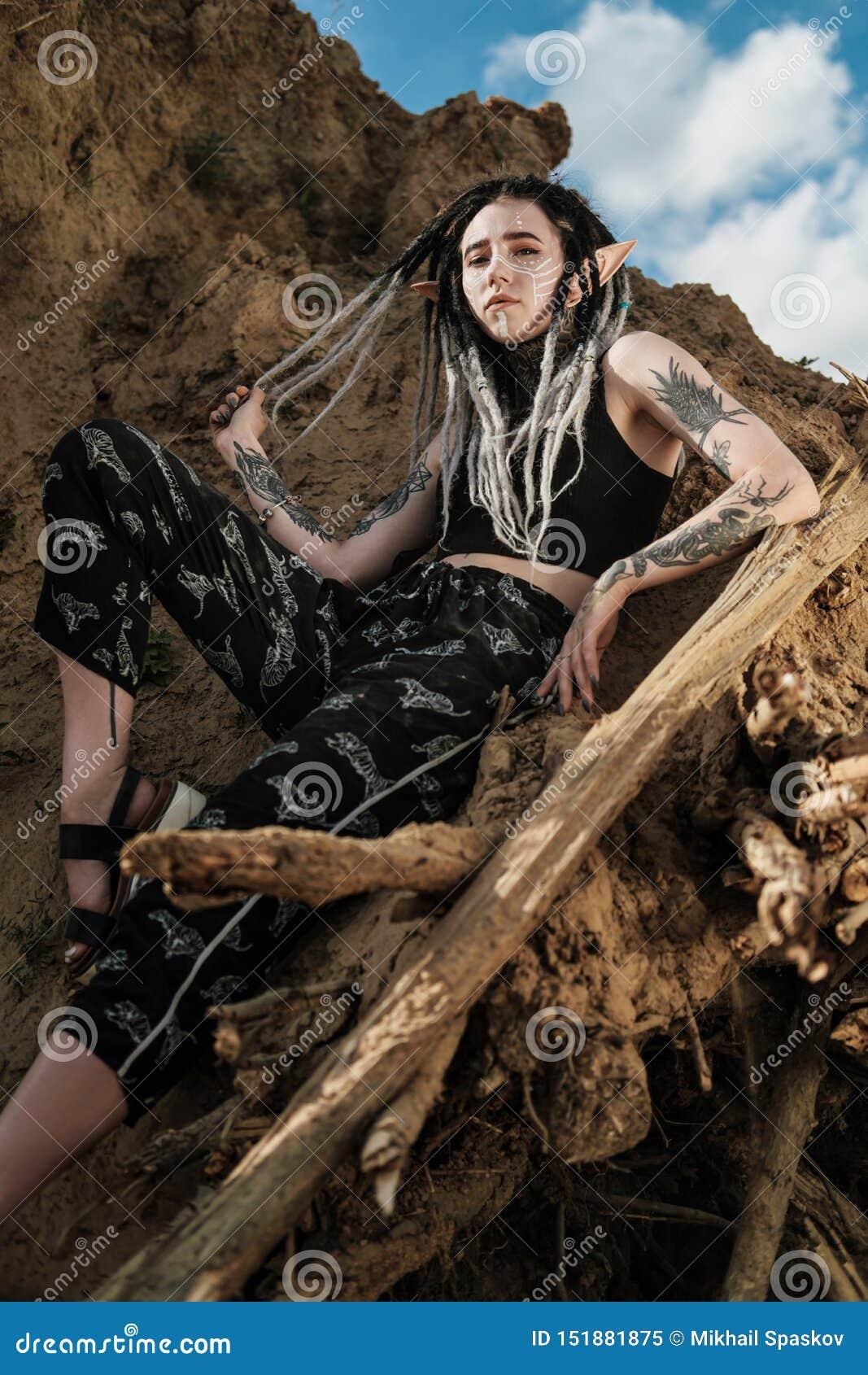Όμορφη προκλητική γυναίκα στο μαύρο εσώρουχο Το σώμα καλύπτεται με πολλές δερματοστιξίες Dreadlocks στο κεφάλι Τοποθέτηση ενάντια