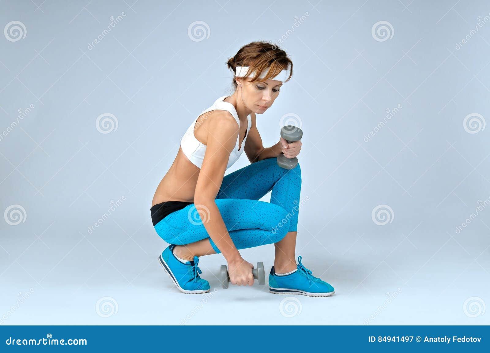 Όμορφη προκλητική γυναίκα αθλητικής ικανότητας που κάνει workout την άσκηση με το δ