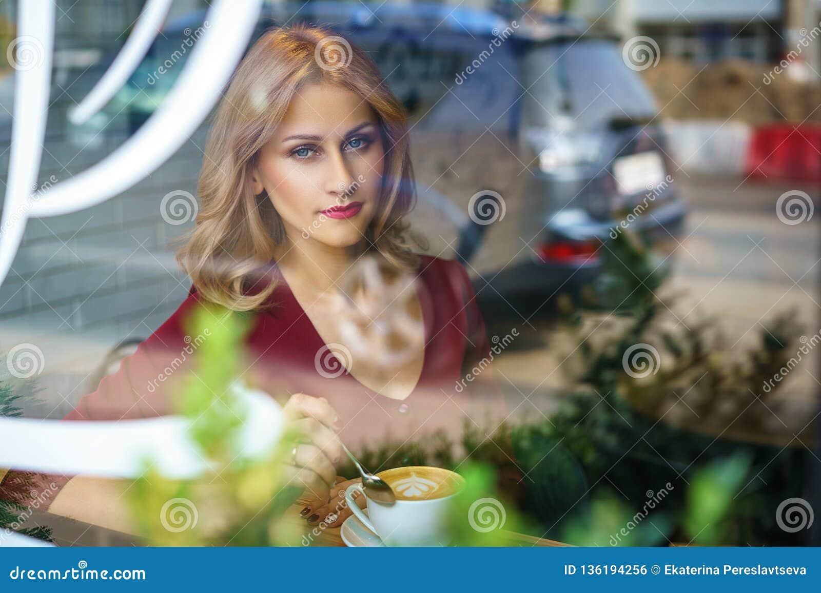 Όμορφη συνεδρίαση γυναικών από το παράθυρο σε έναν καφέ κατανάλωσης καφέδων