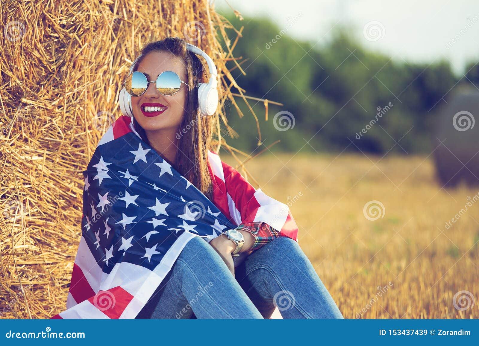 Όμορφη συνεδρίαση κοριτσιών στον τομέα, με μια σημαία των Ηνωμένων Πολιτειών της Αμερικής στους ώμους της