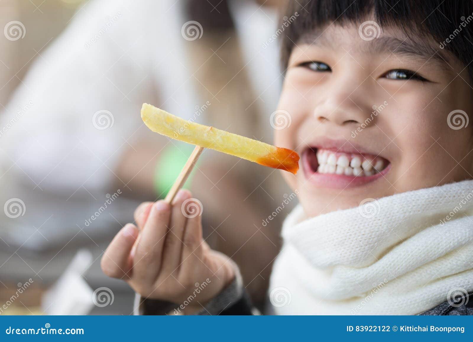 Όμορφη συνεδρίαση μικρών κοριτσιών γέλιου στον πίνακα και κατανάλωση των τηγανιτών πατατών