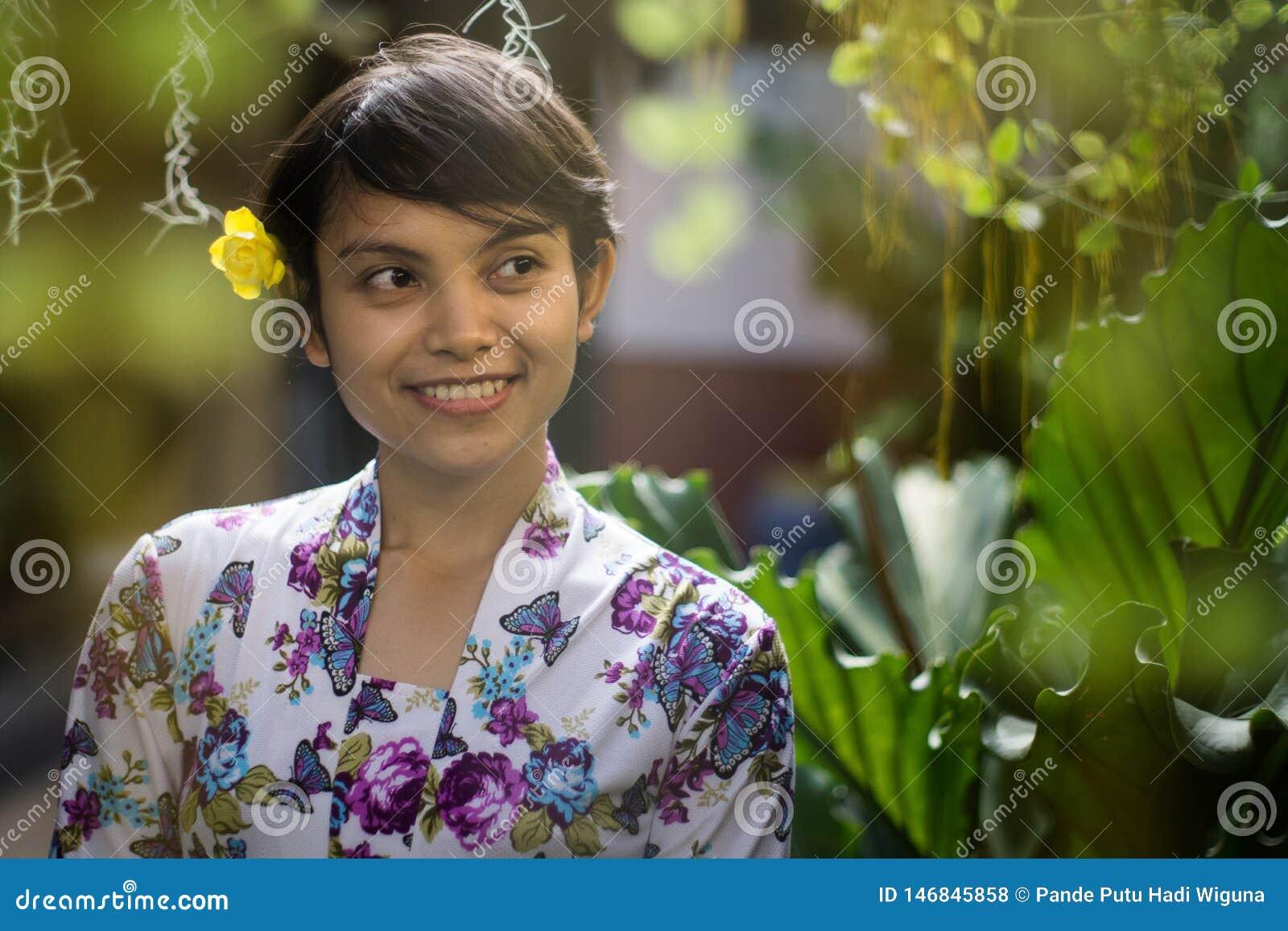 Όμορφη σύντομη μυρωδιά κοριτσιών τρίχας ασιατική ινδονησιακή με το πράσινο υπόβαθρο φύσης Αυτή που χρησιμοποιεί το floral παραδοσ