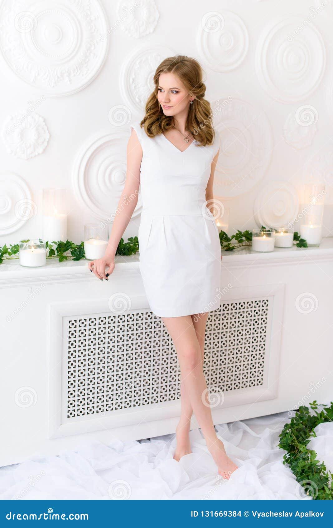 Όμορφη τοποθέτηση νέων κοριτσιών για μια εικόνα, άσπρο φόρεμα που συσχετίζει με τους καθαρούς τοίχους, μακριά λεπτά πόδια που δια