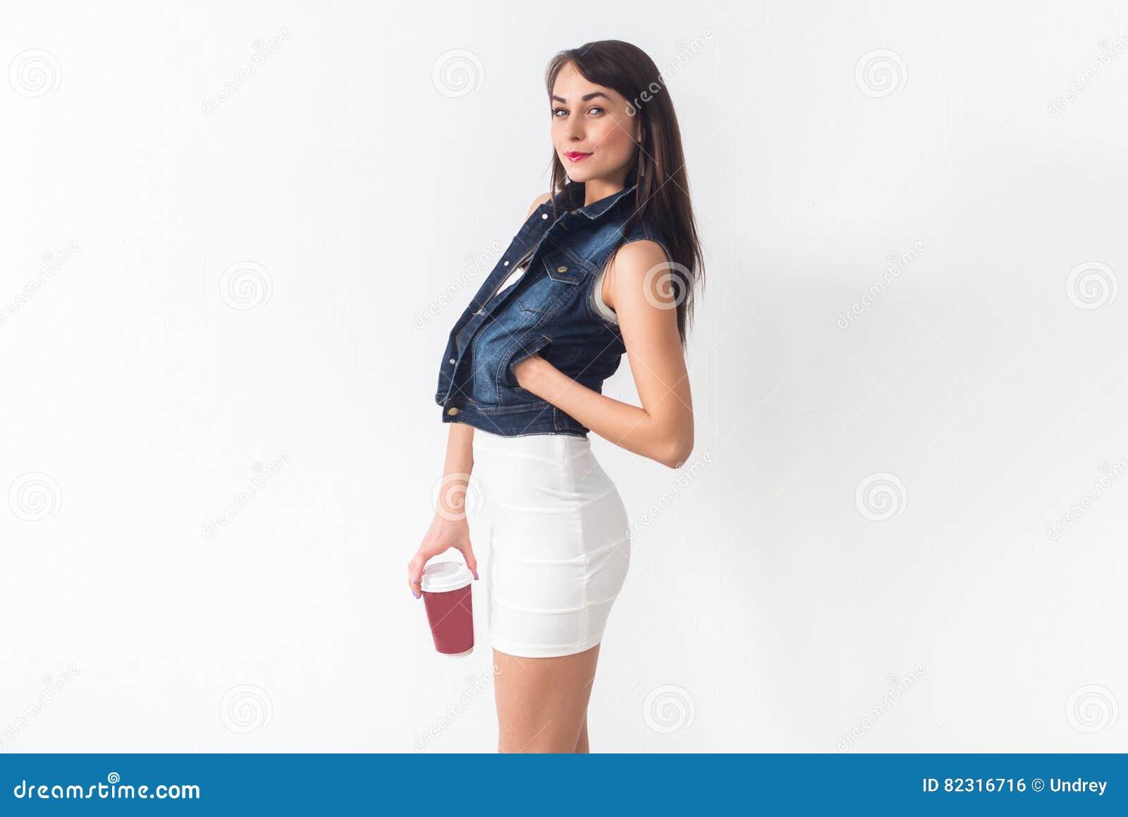 Όμορφη τοποθέτηση brunette στα περιστασιακά μοντέρνα ενδύματα στο άσπρο υπόβαθρο, που κρατά το κόκκινο φλυτζάνι του take-$l*away