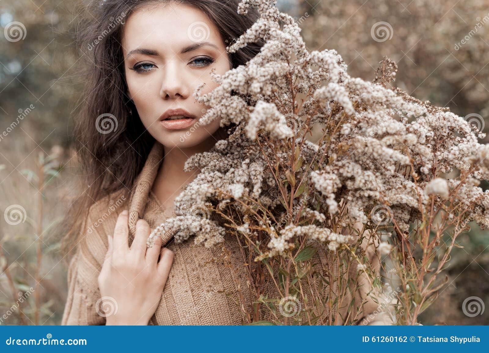 Όμορφη λυπημένη χαριτωμένη ελκυστική γυναίκα σε ένα μπεζ πουλόβερ ευρέως σε έναν τομέα της ξηράς χλόης στην κρύα συννεφιάζω ημέρα