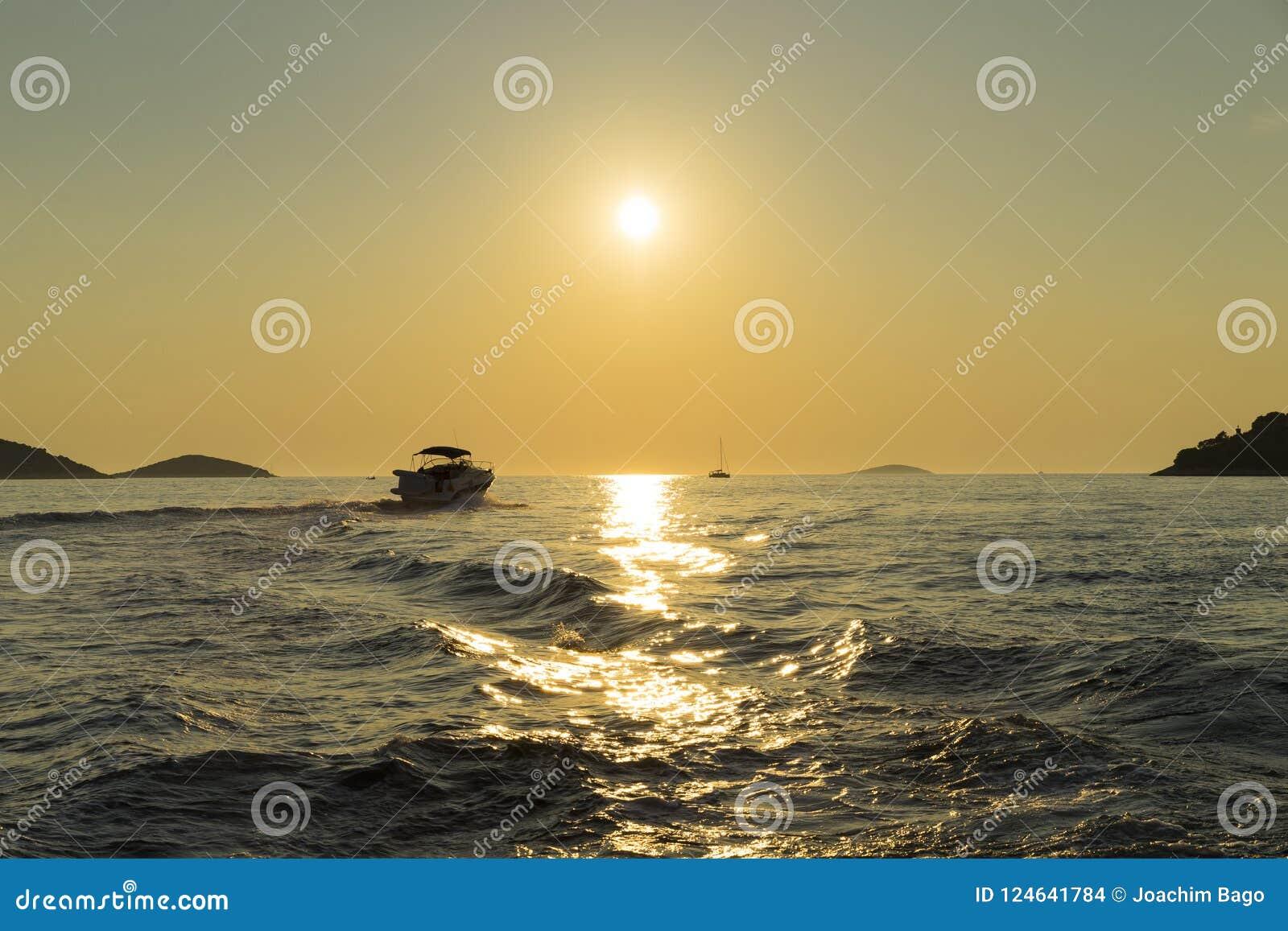Όμορφη φωτογραφία φύσης και τοπίων της βάρκας στο ηλιοβασίλεμα στην αδριατική θάλασσα στην Κροατία
