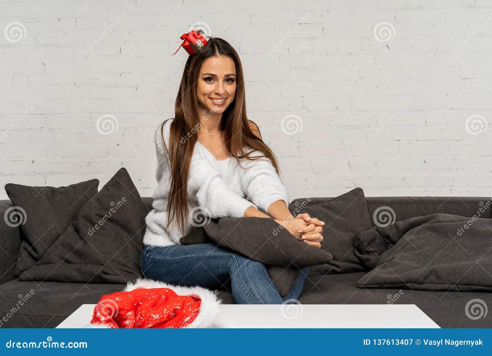 Όμορφη χαριτωμένη γυναίκα στη συνεδρίαση καπέλων santa στον καναπέ και την τοποθέτηση με το πρόσωπο χαμόγελου