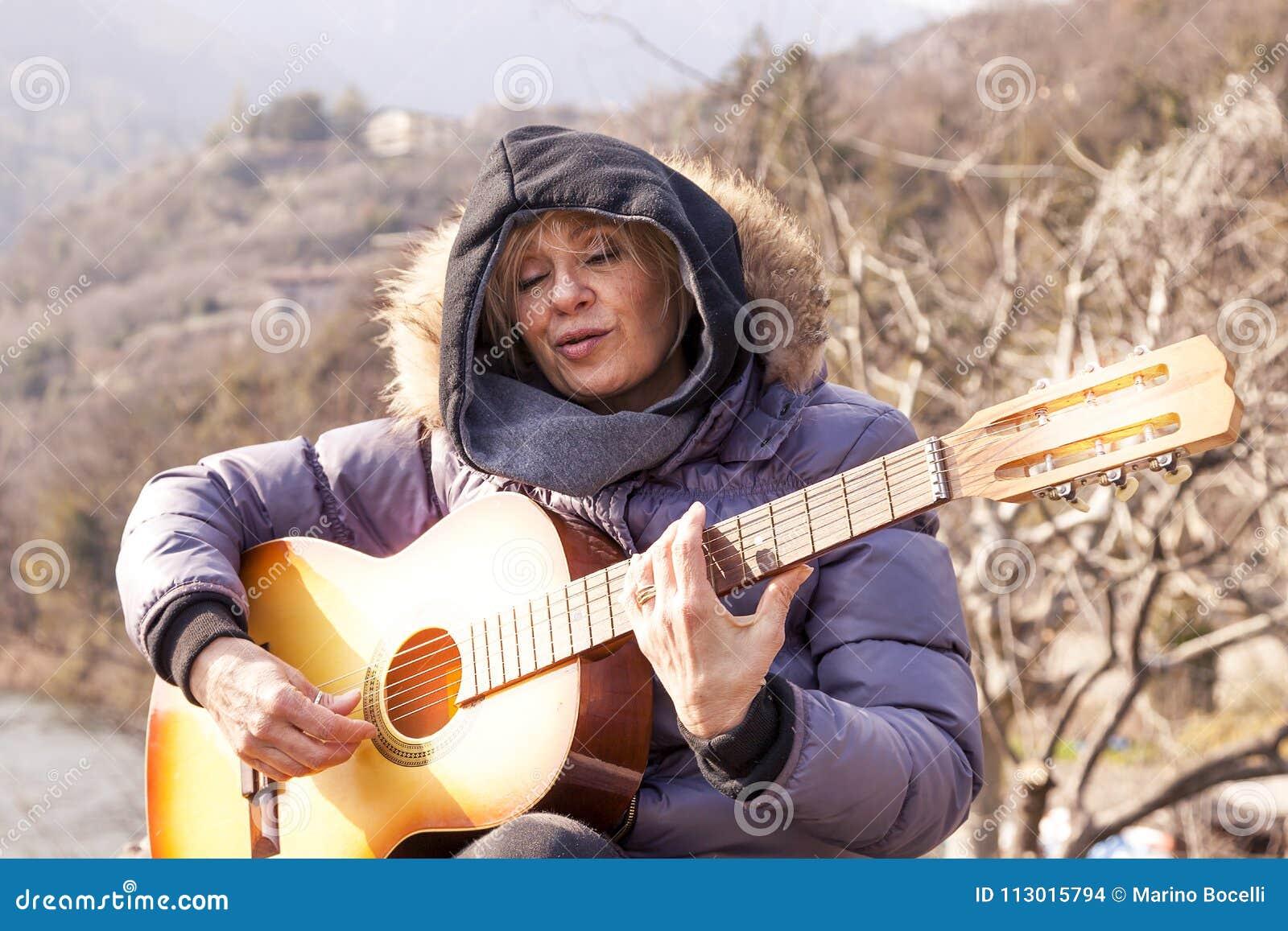 Όμορφη ώριμη γυναίκα που παίζει μια συνεδρίαση κιθάρων σε έναν βράχο
