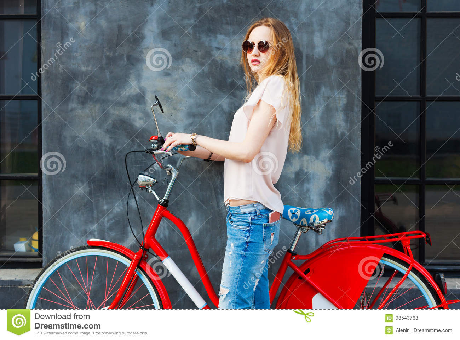 Όμορφη long-legged τοποθέτηση κοριτσιών με το κόκκινο εκλεκτής ποιότητας ποδήλατο Έχει ένα smartphone στην τσέπη τζιν της