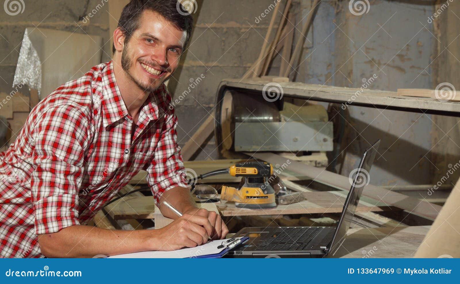 Όμορφος αρσενικός ξυλουργός που χαμογελά στη κάμερα στο εργαστήριό του