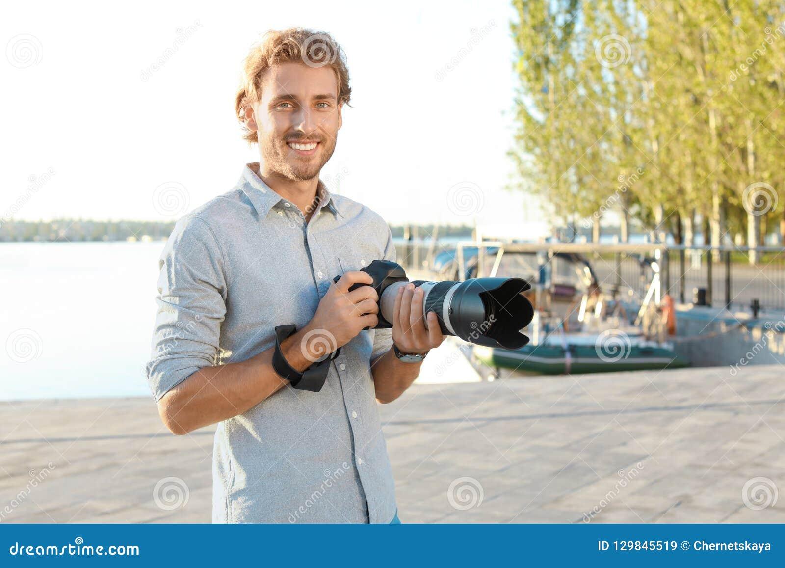 Όμορφος αρσενικός φωτογράφος που κρατά την επαγγελματική κάμερα στην αποβάθρα
