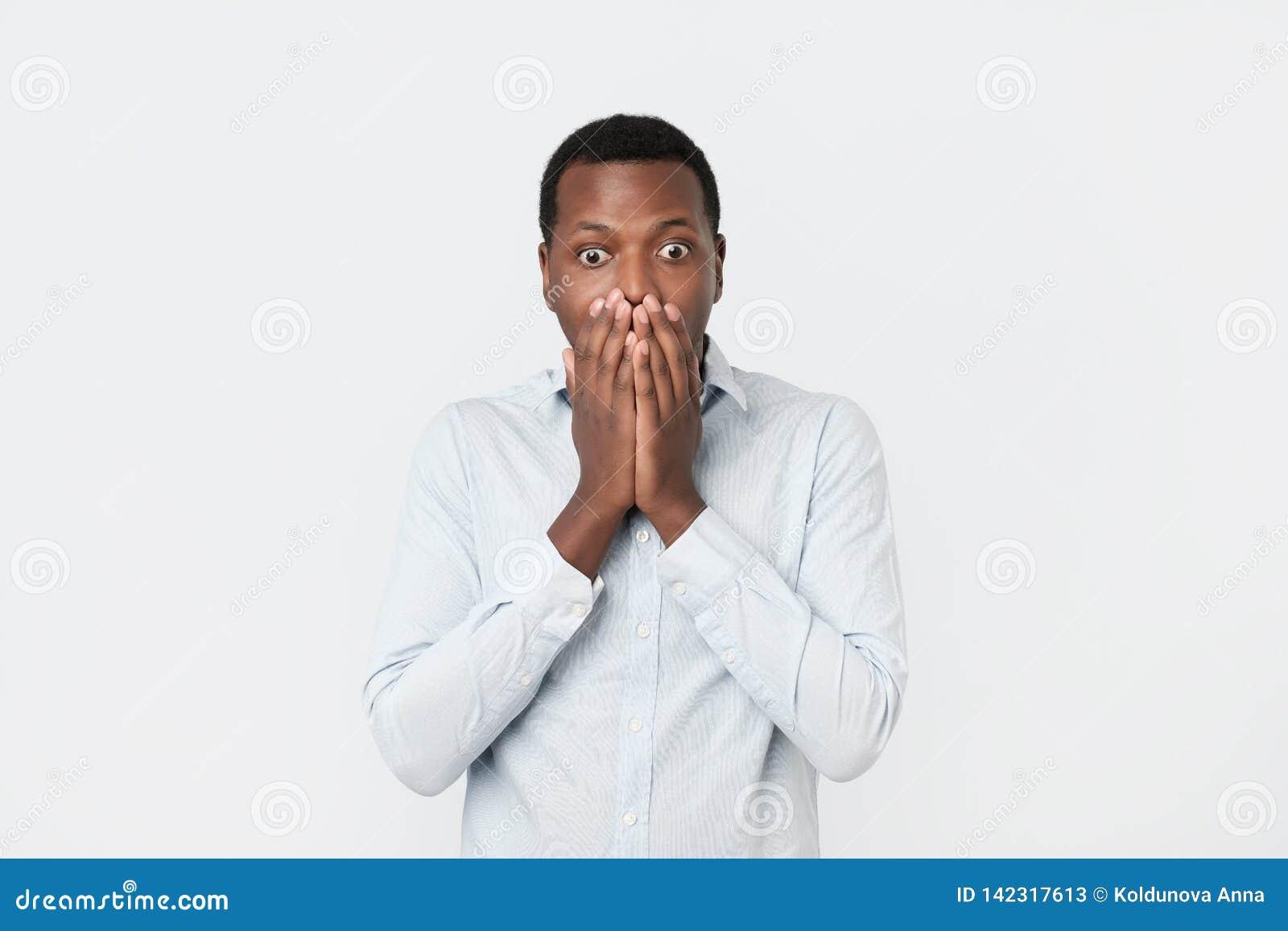 Όμορφος αφρικανικός μαύρος που καλύπτει το στόμα με το χέρι