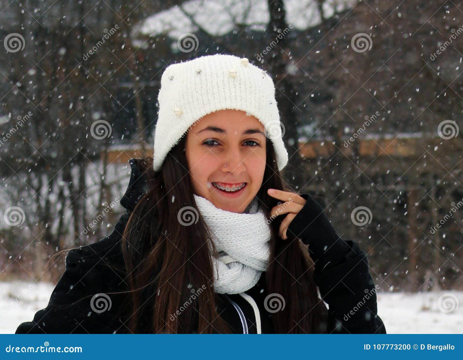 Όμορφος βέβαιος πράσινος έφηβος ματιών που περπατά κάτω από το χιόνι χιονίζοντας