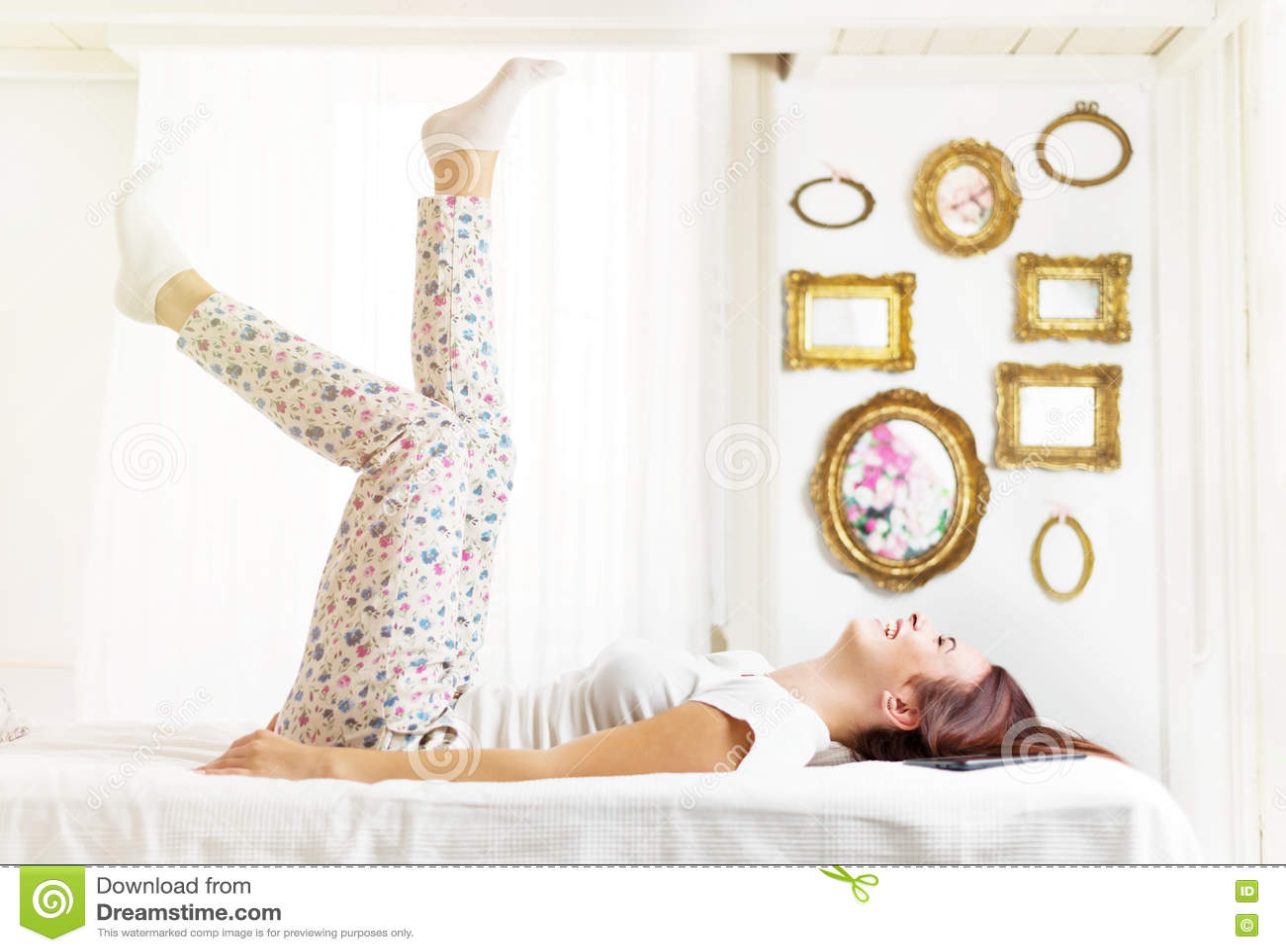 Όμορφος, ευτυχής, γυναίκα που βάζει στο κρεβάτι σε ένα φωτεινό δωμάτιο